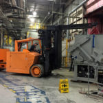 BSM forklift operator moving massive grinder into position for installation