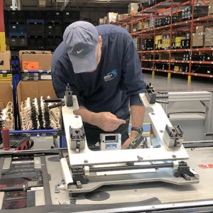 BSM support staff member performing preventative maintenance on pallets for car seat production