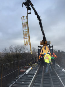 boom lowering cage ladder into place on bridge repair site